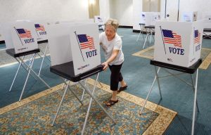 A Florida poll worker arranges voting booths. (2010 Tampa Bay Times photo)