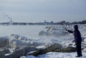 "Someone takes a picture along the shore of Lake Michigan with temperatures in the negative digits on Jan. 7, 2014, in Milwaukee. A ""polar vortex"" of frigid air centered on the North Pole had dropped temperatures precipitously. (Getty Images)"