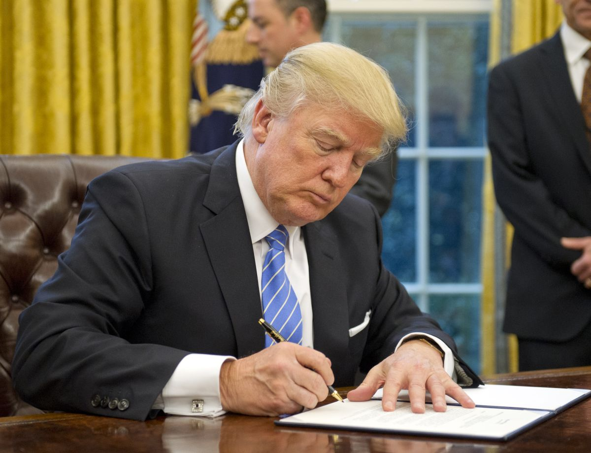 U.S. President Donald Trump signs the last of three Executive Orders in the Oval Office of the White House in Washington, DC on Monday, January 23, 2017. (Photo by Ron Sachs - Pool/Getty Images)