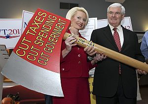 Former House Speaker Newt Gingrich, with his wife Callista, holds an oversize replica of an ax after signing a pledge to cut government Oct. 25 in Concord, N.H.