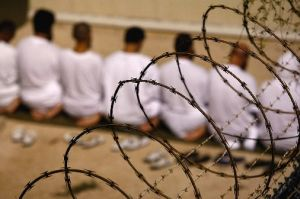 """A group of detainees kneels during an early morning Islamic prayer in their camp at the U.S. military prison for """"enemy combatants"""" in Guantanamo Bay, Cuba. President Barack Obama approved the resumption of military trials for detainees."""