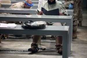 "This 2010 photograph, made through one-way glass and reviewed by the U.S. military, shows a shackled Guantanamo detainee reading his materials in a ""Life Skills"" class as guards behind him shackle another detainee to the floor after bringing him to class."