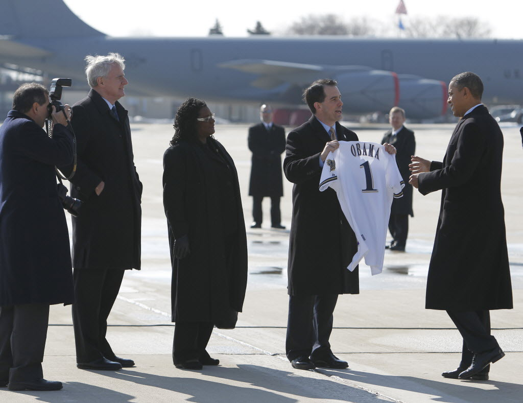 Gov. Scott Walker presented President Barack Obama with a Milwaukee Brewers jersey when Obama arrived at the Milwaukee airport on Feb. 15, 2012. Mayor Tom Barrett and U.S. Rep. Gwen Moore looked on.