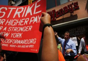 New York City Councilman Brad Lander speaks to employees at Wendy's fast-food restaurant during a demonstration outside of one of the restaurants to demand higher pay and the right to form a union on July 29, 2013, in New York City.