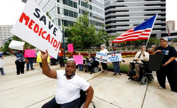 "Mario Henderson leads chants of ""save Medicaid"" outside a Jackson, Miss., building that houses offices of Sen. Thad Cochran, R-Miss., on June 29, 2017.l (AP/Rogelio V. Solis)"