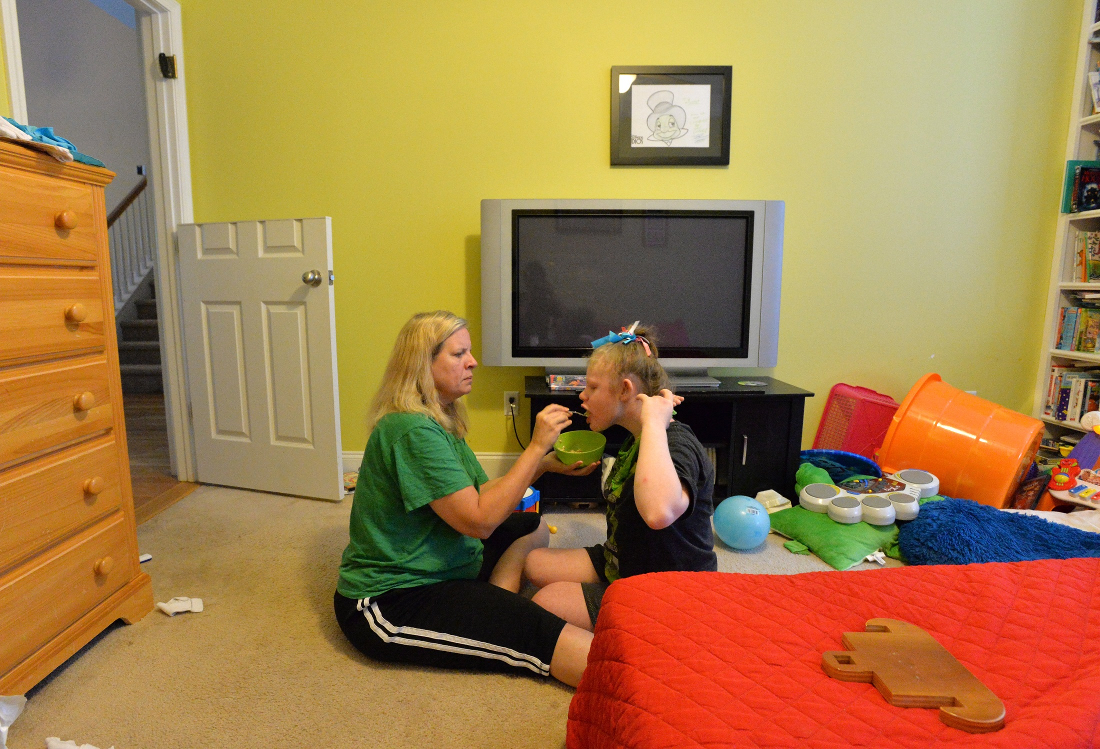 Kelli Hopkins feeds her daughter Michala, 16, in their Covington home in September. Michala suffer from a seizure disorder that could be treated by cannabis-based oil that may become legal in Georgia.