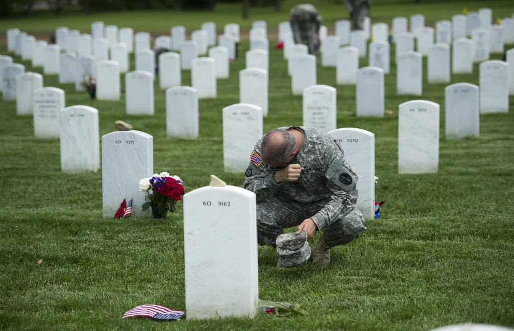 An Army colonel wipes away tears as he visits a grave at Arlington National Cemetery while placing flags at grave sites ahead of Memorial Day 2014.
