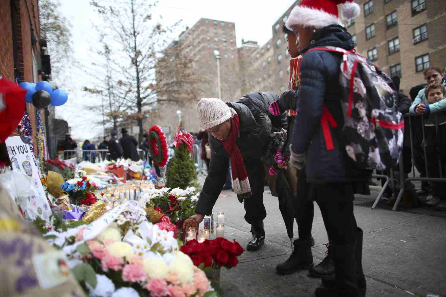 A family visits a makeshift memorial for two New York City police officers killed on Dec. 20. (New York Times Photo)