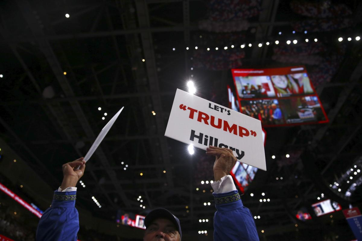 An attendee holds signs on the final day of the Republican National Convention at the Quicken Loans Arena in Cleveland, July 21, 2016. (New York Times)