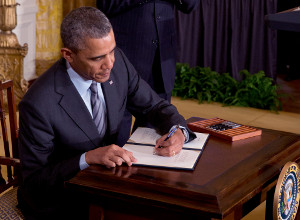 President Barack Obama signs an executive memorandum instructing the government to avoid discriminating against job applicants among America's long-term unemployed, at the White House in Washington, Jan. 31, 2014. (New York Times)