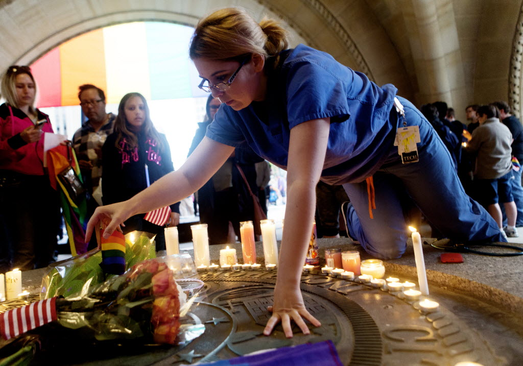A woman places an LGBTQ flag in the middle of a circle of candles and roses during a vigil held for victims of the Orlando mass shooting at Milwaukee City Hall on June 13, 2016. (Calvin Mattheis photo)