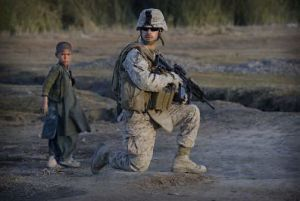 An Afghan boy stands next to a United States Marine during an operation in the volatile Helmand province of southern Afghanistan. For most Americans, a war like the one in Afghanistan tests the traditional boundaries of wartime and peacetime.