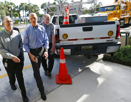 Florida Gov. Rick Scott, center, walks with Florida Department of Transportation (FDOT) workers as he arrives at a news conference at the FDOT District Four Office, Wednesday, Aug. 22, 2018, in Fort Lauderdale, Fla. (AP)