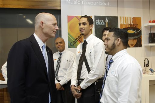 Gov. Rick Scott, left, talks to recently hired store employees Giancarlo Colon, right, and Demetrio Gomez, second from right, during the opening of a new AT&T store, Wednesday, Oct. 30, 2013, in Miami. (AP)
