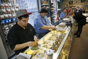 Employees roll joints behind the sales counter at Medicine Man marijuana dispensary in Denver, Colo. Recreational pot became legal this year. (AP)