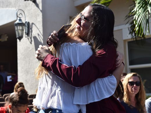 Friends embrace in tears before the start of a community prayer vigil for Marjory Stoneman Douglas High School shooting victims. (Eric Hasert/USA Today Network)