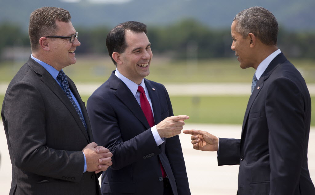 President Barack Obama is greeted by Wisconsin Gov. Scott Walker (middle) and La Crosse, Wis., Mayor Tim Kabat as he arrives at a La Crosse airport on July 2, 2015. Walker is expected to announce his run for president on July 13, 2015. (AP photo)