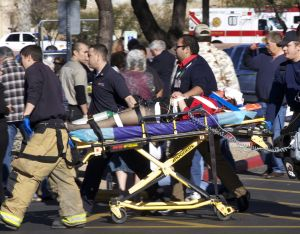 Emergency personnel use a stretcher to carry a shooting victim outside a shopping center in Tucson, Ariz. on Saturday, Jan. 8, 2011 where U.S. Rep. Gabrielle Giffords, D-Ariz., and others were shot as the congresswoman was meeting with constituents.