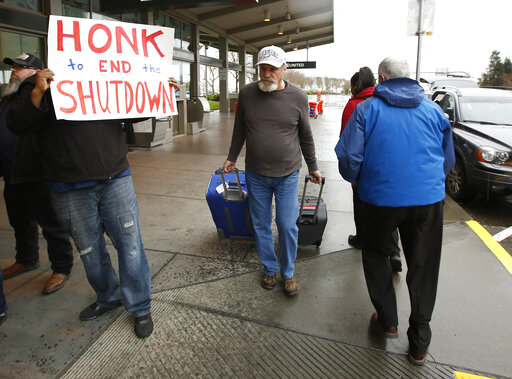 A man heading into the Sacramento International Airport passes demonstrators calling for President Donald Trump and Washington lawmakers to end the shutdown. (AP Photo/Rich Pedroncelli)
