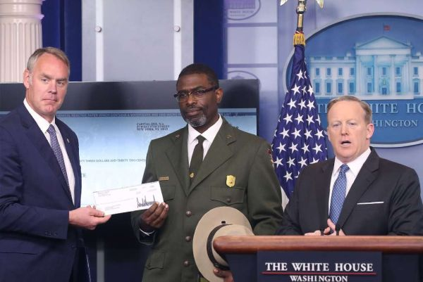 White House press secretary Sean Spicer (right) gives Interior Secretary Ryan Zinke (left) the first-quarter earnings of President Donald Trump as Harpers Ferry National Historical Park Superindendent Tyrone Brandyburg looks on. (Mark Wilson/Getty Images)