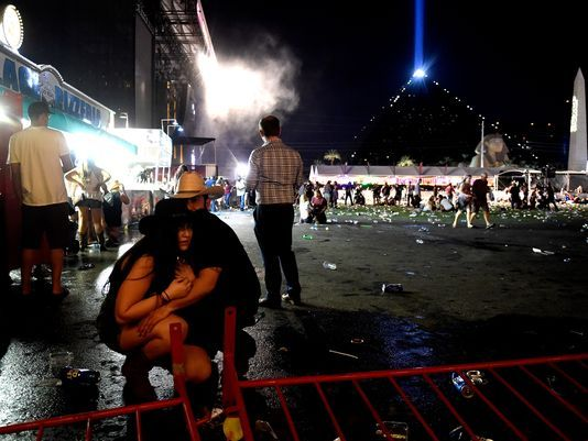 People take cover after hearing gunfire at a country music festival, the scene of the mass shooting. (David Becker/Getty Images