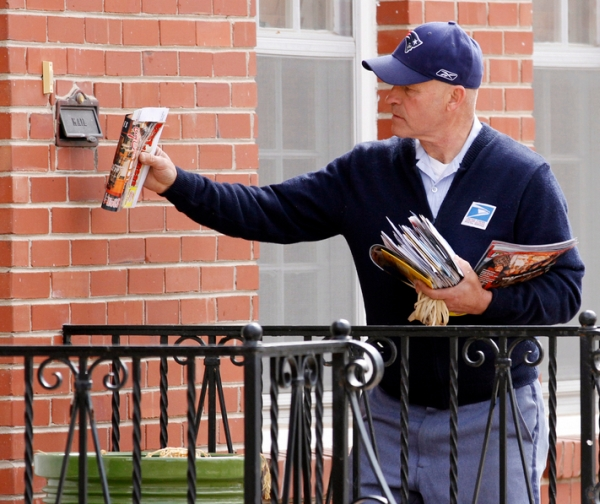 Russ Fox, a letter carrier for the U.S. Postal Service, delivers mail in Wichita, Kan. (Associated Press)