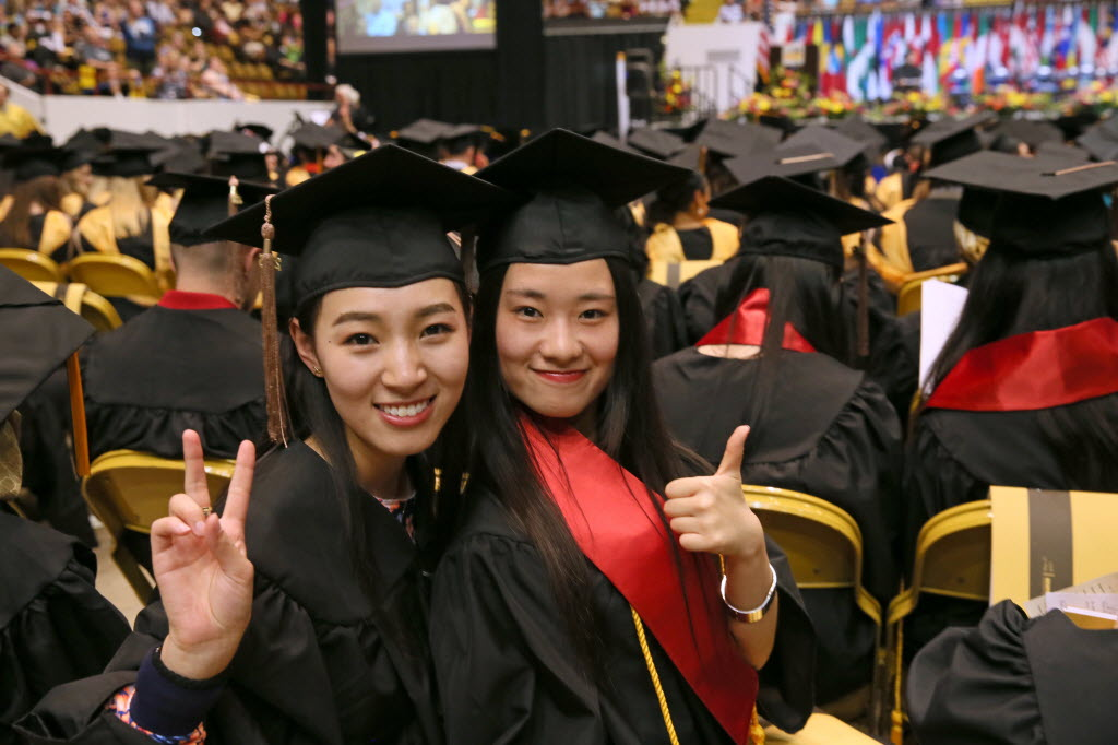 Yixuan Wang (left) and Ke Xiao celebrated their graduation from the University of Wisconsin-Milwaukee, one of the UW System campuses, on May 17, 2015. The UW System faces cuts under the proposed 2015-'17 Wisconsin state budget. (Michael Sears photo)