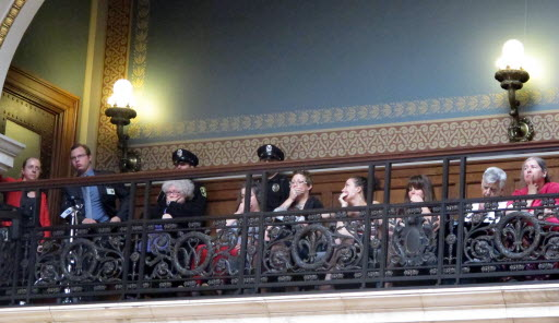 In silent protest, opponents of a series of Republican-backed bills dealing with abortions hold their hands over their mouths while watching debate in the state Assembly on June 13, 2013. AP photo by Scott Bauer
