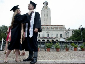 Annelise Schuessler adjusts the cap and gown of fellow graduate Garrett Dee at the May commencement celebration at the University of Texas at Austin, an institution not listed among those with $10,000 degrees. (Andy Sharp, for Austin American-Statesman).