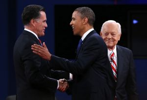 Barack Obama and Mitt Romney shake hands at the final presidential debate. Moderator Bob Schieffer looks on.