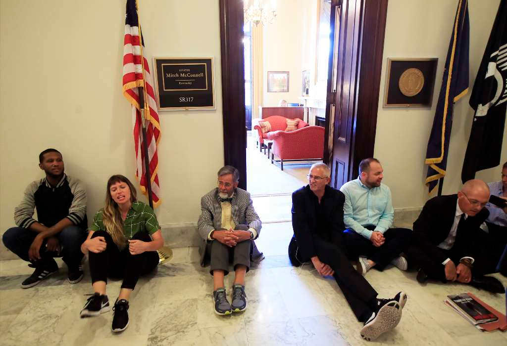 Protesters against the Republic health care proposals sit outside the office of Senate Majority Leader Mitch McConnell. (AP)