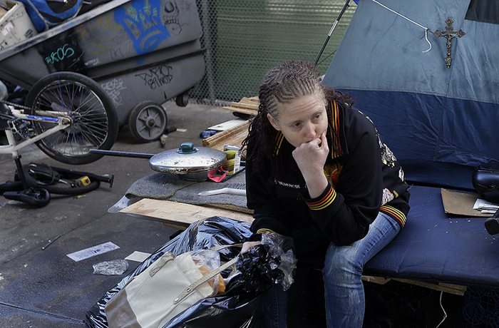 A homeless woman sits with a bag containing her belongings in March 2016 in San Francisco. (AP Photo/Ben Margot)
