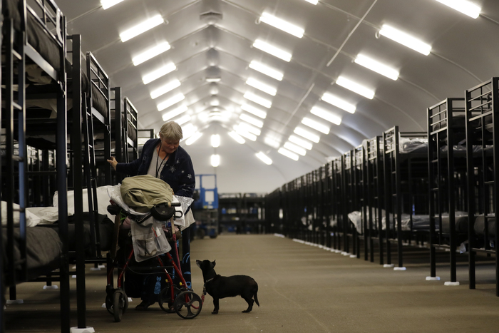 Verna Vasbinder prepares her new bunk in downtown San Diego's Temporary Bridge Shelter for the homeless in December 2017 as her dog, Lucy Lui, looks on. (AP Photo/Gregory Bull)