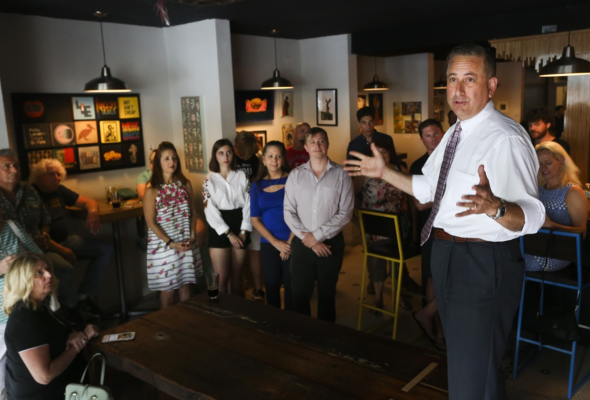St. Petersburg Mayor Rick Kriseman (right) stands up on a bench as he greets customers and supporters while talking about the stakes in the election during a campaign style stop at Cycle Brewing in St. Petersburg on June 6. (DIRK SHADD | Tampa Bay Times)