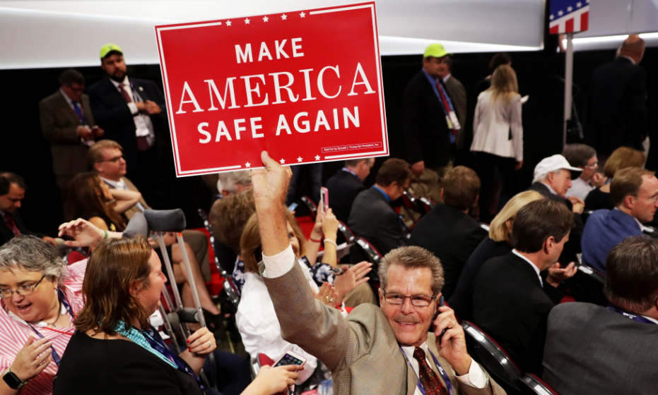 "A delegate holds a sign that reads ""Make America Safe Again"" prior to the start of the evening session on the first day of the Republican National Convention on July 18, 2016 at the Quicken Loans Arena in Cleveland, Ohio. (Getty)"