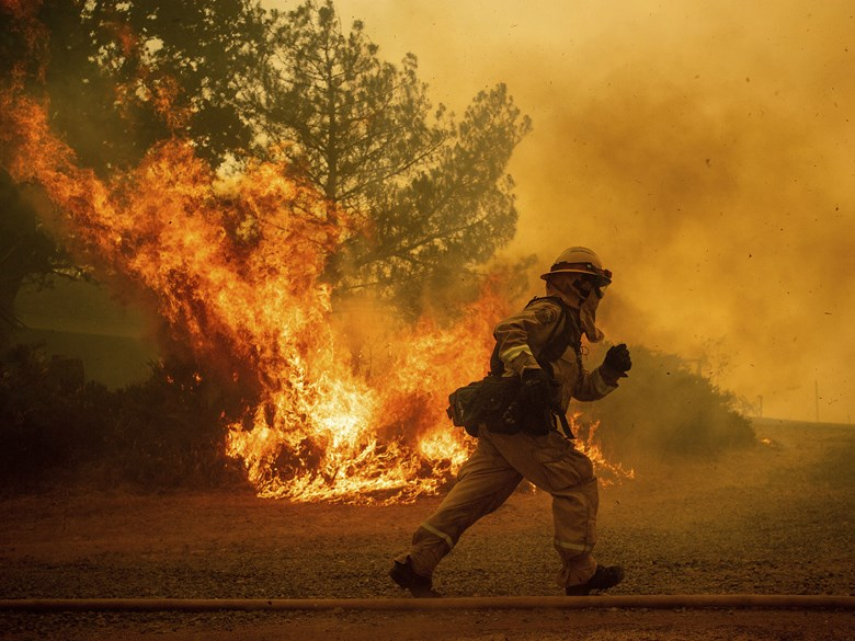A firefighter runs while trying to save a home as a wildfire tears through Lakeport, Calif. on Tuesday, July 31, 2018. AP Photo / Noah Berger