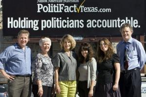Members of the original PolitiFact Texas team pause before a billboard (American-Statesman photo, Deborah Cannon).
