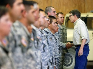 Gov. Rick Perry shakes hands with National Guard troops training at Camp Swift in Bastrop, Texas Aug. 13, 2014 before they deployed to the Texas-Mexico border region (Associated Press photo).
