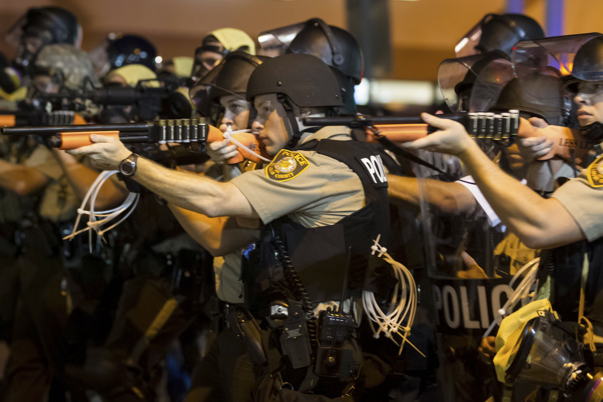 Police aim their weapons and make their way down West Florissant Avenue, pushing protesters north on the street in Ferguson, Mo., the night of Aug. 18, 2014. (New York Times)