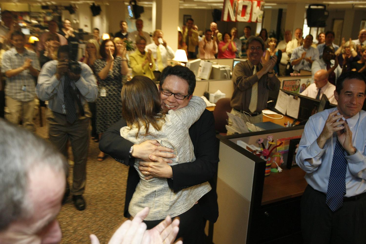 PolitiFact Founder Bill Adair receives congratulations from Reporter and Researcher Angie Drobnic Holan in the newsroom of the St. Petersburg Times.