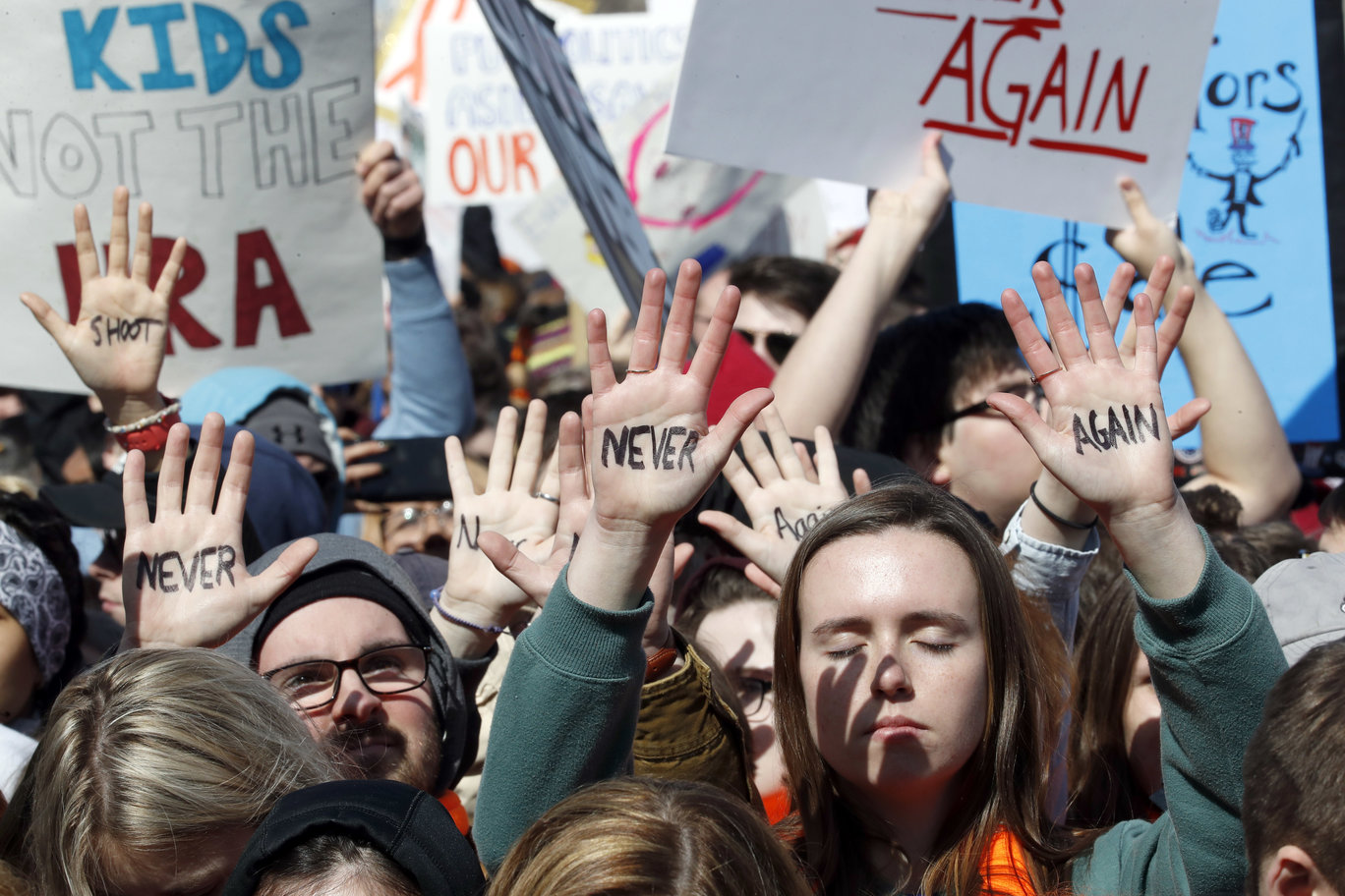 People hold their hands up with messages written on them during the March For Our Lives rally in support of gun control March 24, 2018, in Washington. (AP)