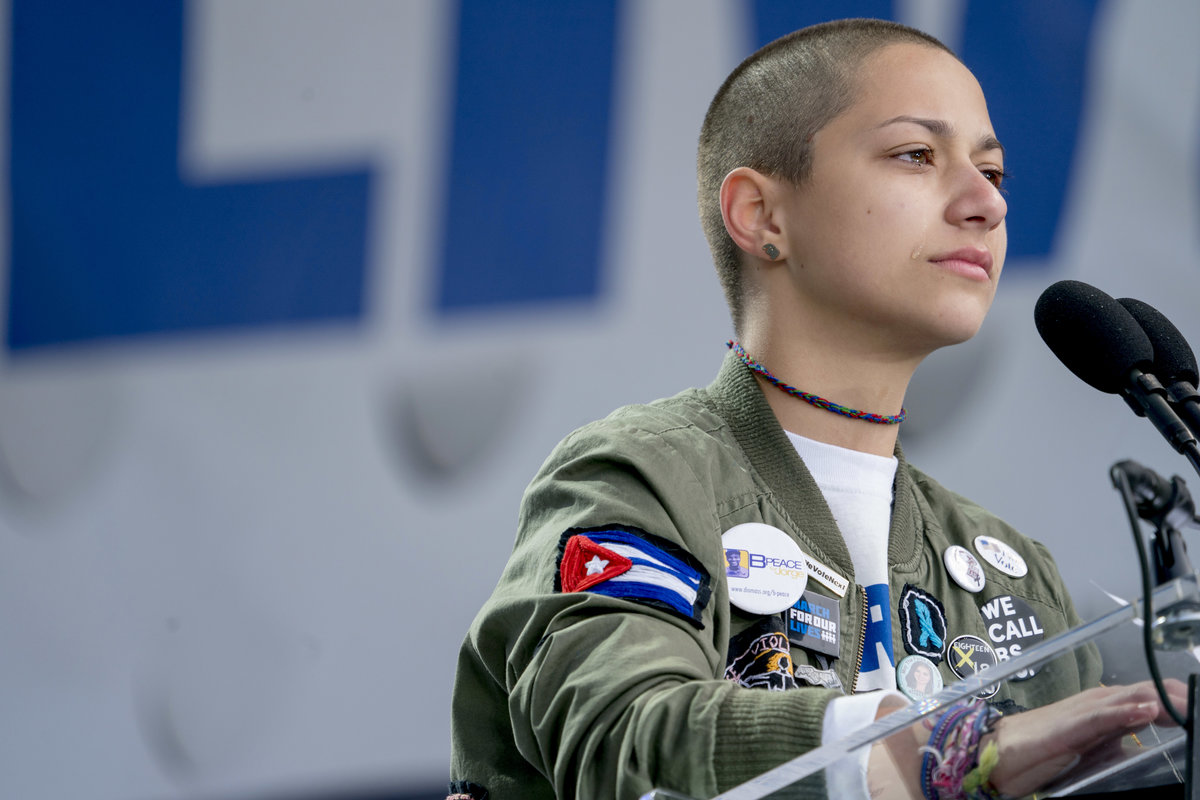 """Emma Gonzalez, a survivor of the mass shooting at Marjory Stoneman Douglas High School in Parkland, Fla., stands silently at the podium during the """"March for Our Lives"""" rally in support of gun control in Washington on March 24, 2018. (AP Photo/Andrew Harn"""