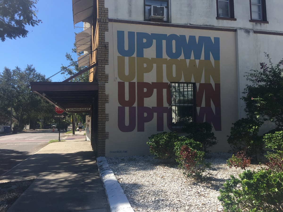 """A sprawling geometric mural and a new insignia with the word """"Uptown"""" can be seen on the sides of the building that houses the Uptown Laundromat. (Photo by Allison Graves)"""