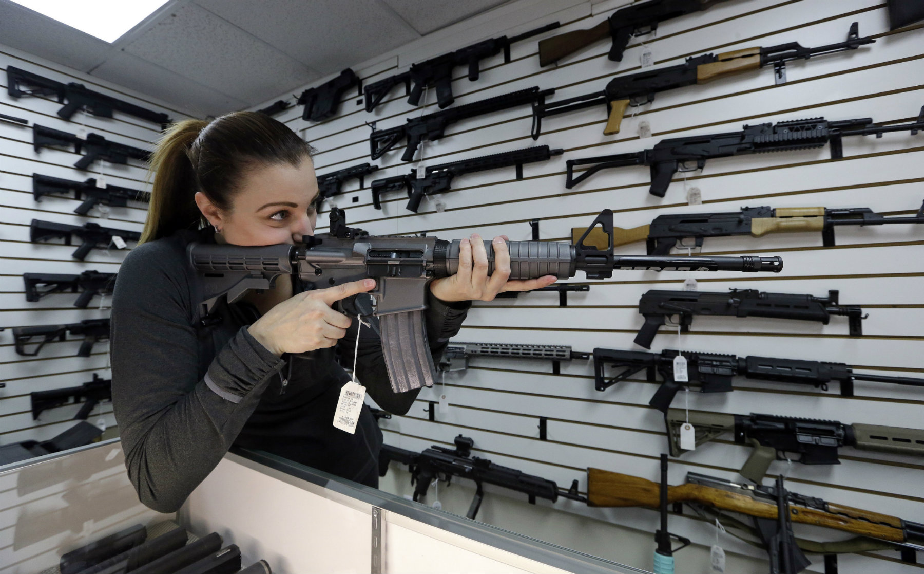 Gun shop owner Tiffany Teasdale-Causer points a Ruger AR-15 semi-automatic rifle in Lynnwood, Wash. (AP Photo/Elaine Thompson)